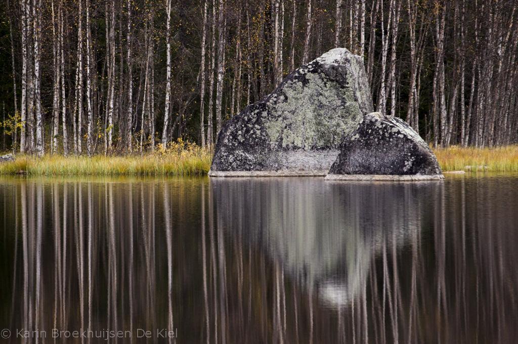 Weerspiegeling van rots in het water
