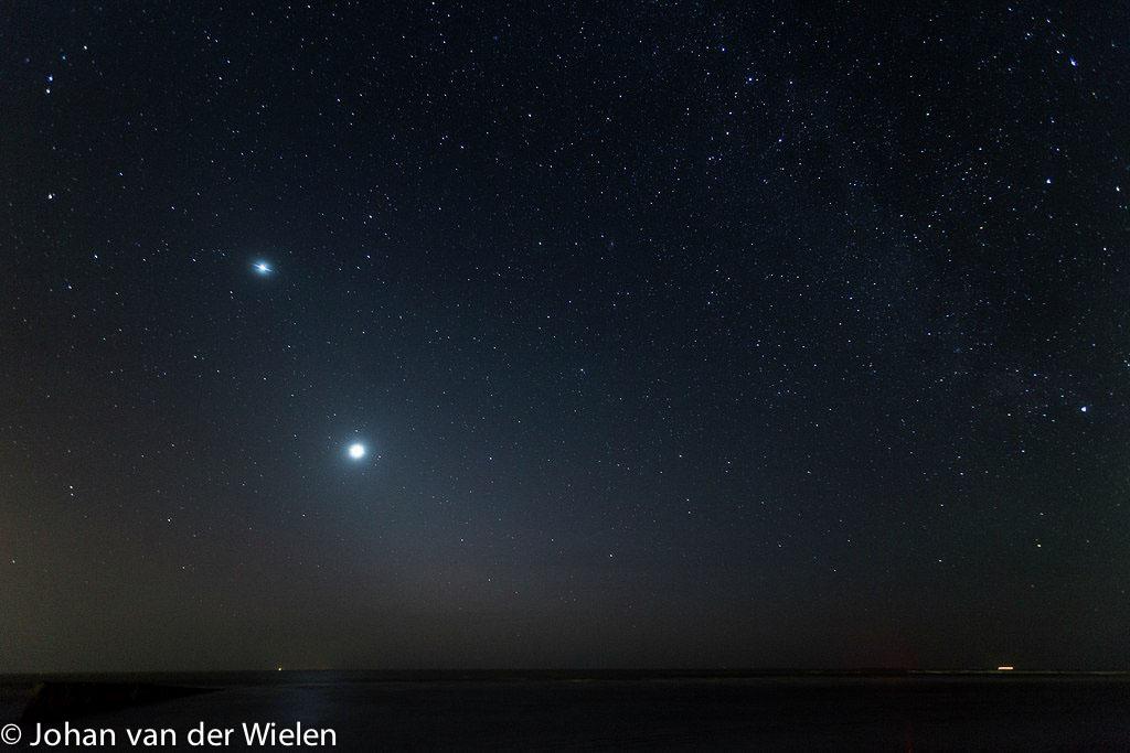 Houten golfbreker in de nacht, aan de hemel de planeten Venus en Jupiter.
