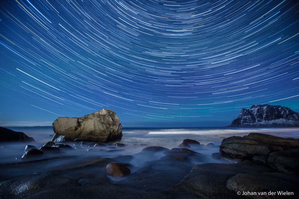 sterrensporen boven zee, Lofoten Noorwegen - De werkelijkheid? Na een uur van sterrensporen waarbij ik een uur lang mijn statief in zee heb laten staan en vast heb moeten houden bij -5 en harde wind doet een Italiaanse 'fotograaf' in de verte zijn groot licht aan als hij wegrijdt... zo van, ik ben klaar en dus maakt het niet meer uit. Achteraf was ik er toch wel blij mee :-)