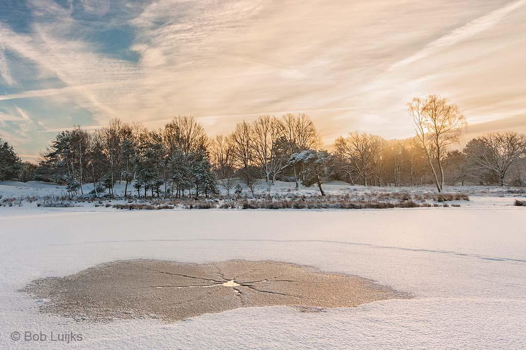 Een wak doorbreekt het sneeuwtapijt.