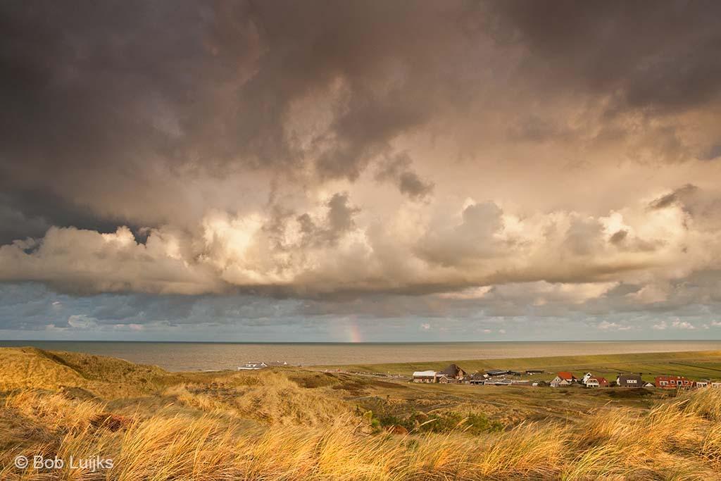 Geef een interessante wolkenlucht alle ruimte. De door de zon aangelichte helmgrassen kleden de voorgrond aan.