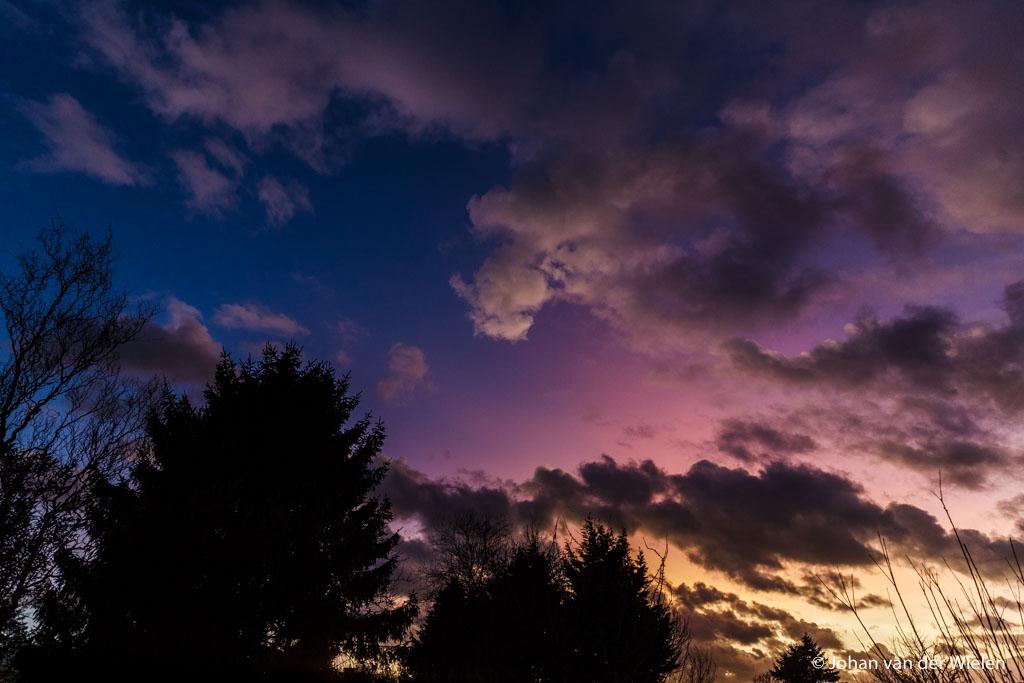 Zeldzame parelmoerwolken, diepe paarskleuring door aanbelichting na zonsondergang.