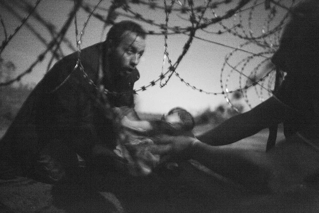 Vluchtelingen vinden een zwakke plek in het hek.
