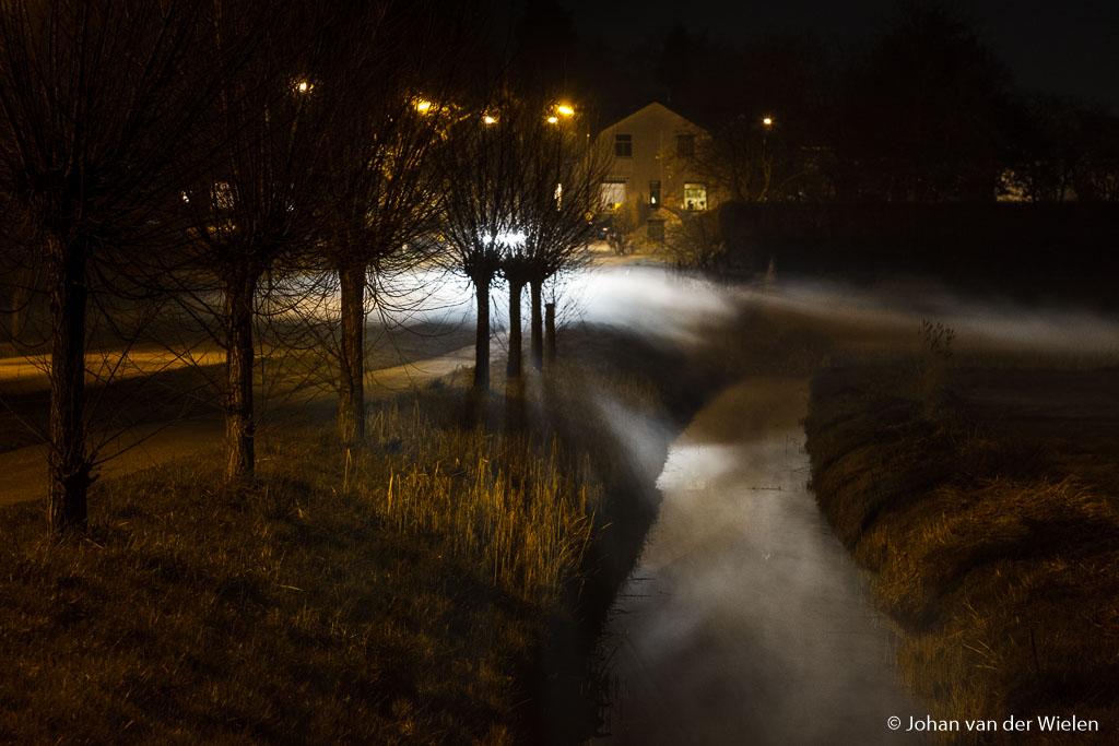 mist boven de sloot in het licht van een aanrijdende auto
