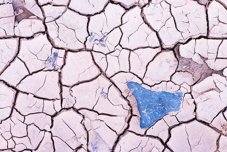 Blauwe steen op droge gebarsten ondergrond