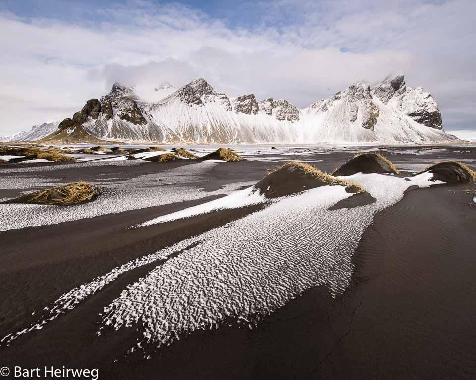 Het gemarmerde patroon van sneeuw en zand neemt de kijker mee het beeld in. De duintoppen fungeren als accenten en laten het oog rondspringen.