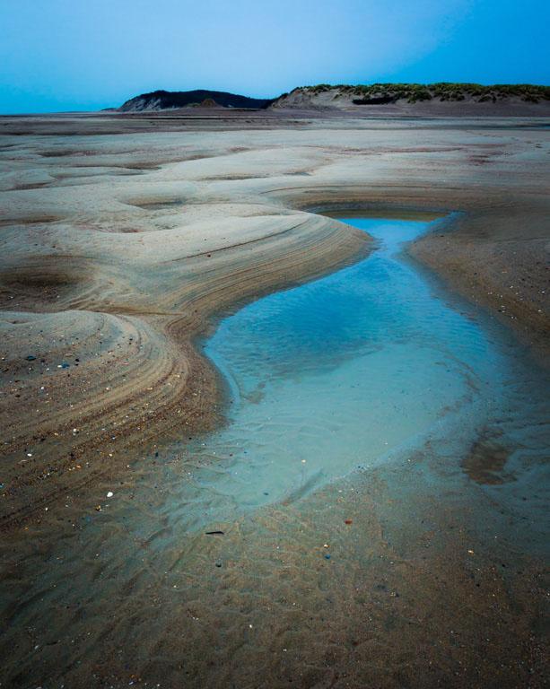 Getijdepoelen op het strand van 't Zwin, gekleurd door het licht aan het einde van de dag.