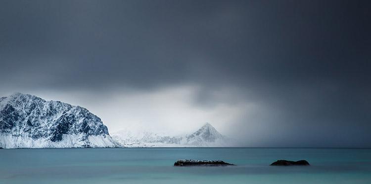 Donkere wolken pakken samen boven de Noorse Zee. Voor nu is het nog even droog op het strand van Haukland op Lofoten, maar dat zal niet lang duren